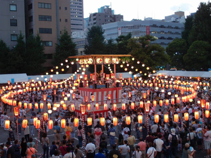 Yagura decorated in red paper lanterns, surrounded by a crowd of people dancing the Bon Odori