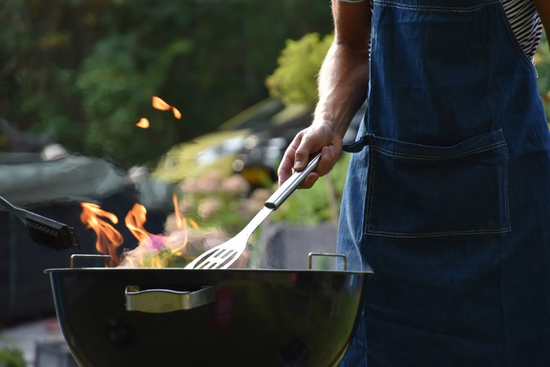 Photo of man wearing blue apron cooking at a barbecue; with only lower half of body