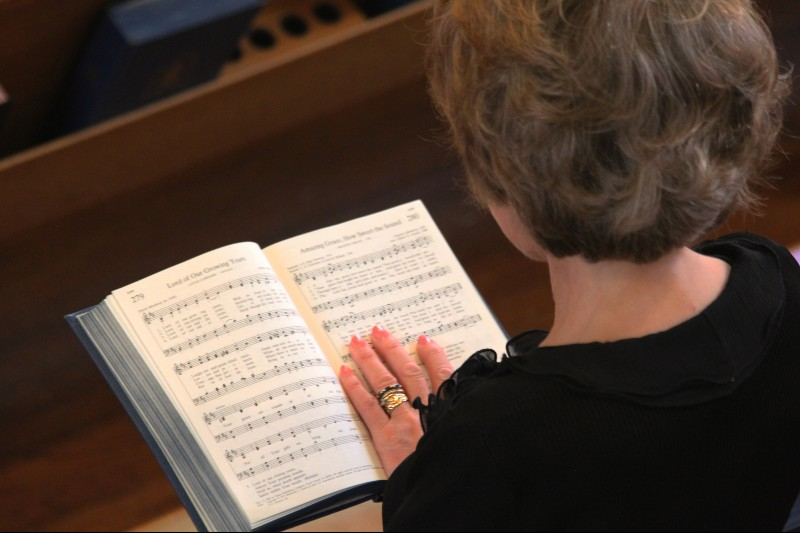 Photo of woman reading music for Amazing Grace, taken from over her shoulder
