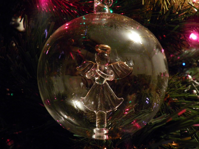 clear glass bauble decorated with the outline of an angel hanging on a Christmas tree