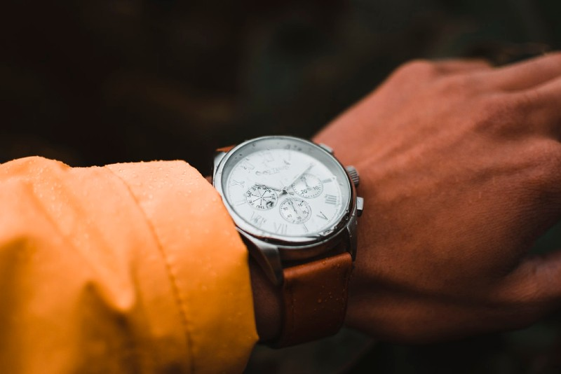 man's arm in an orange shirt wearing a watch