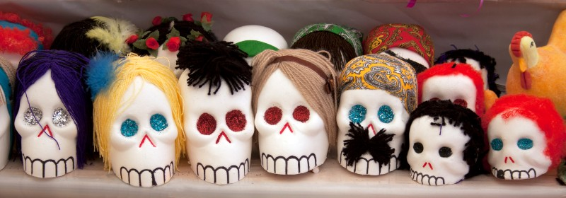Photo of sugar skulls decorated with woolen hair and sequins on a shelf