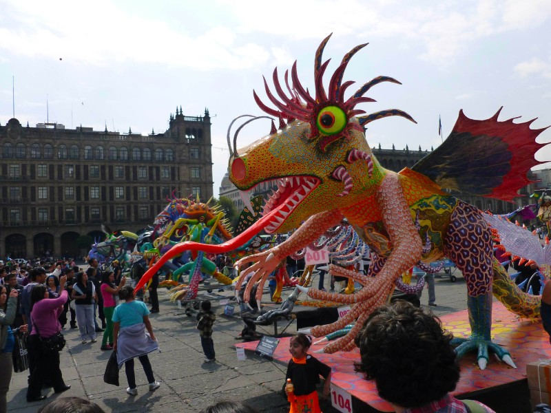 Photo of a large model of a colourful monster, or alebrije, at a Day of the Dead festival