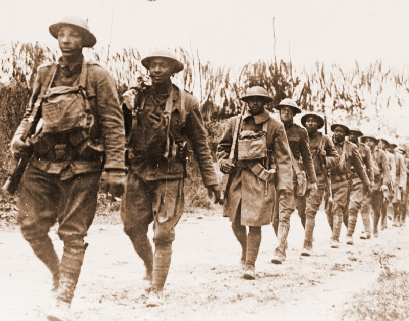 Black and white photos of American soldiers marching in single file at Verdun