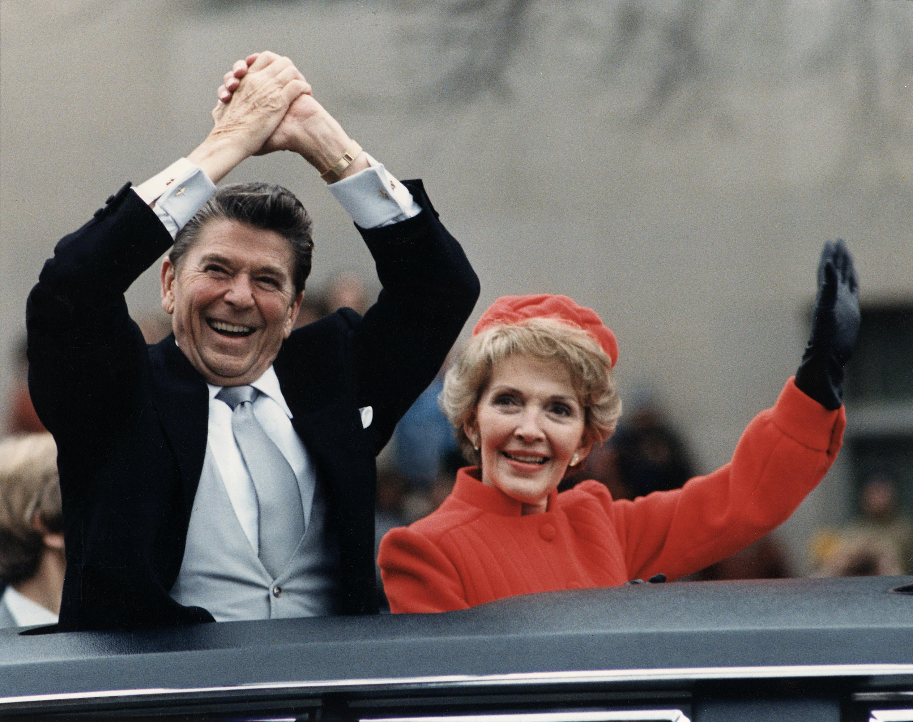 Photo of Ronald Reagan in a limo with his wife cheering at his inauguration