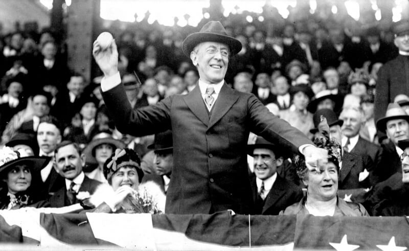 Black and white photograph of Woodrow Wilson cheerfully throwing the first pitch from a stand at a baseball game watched by spectators