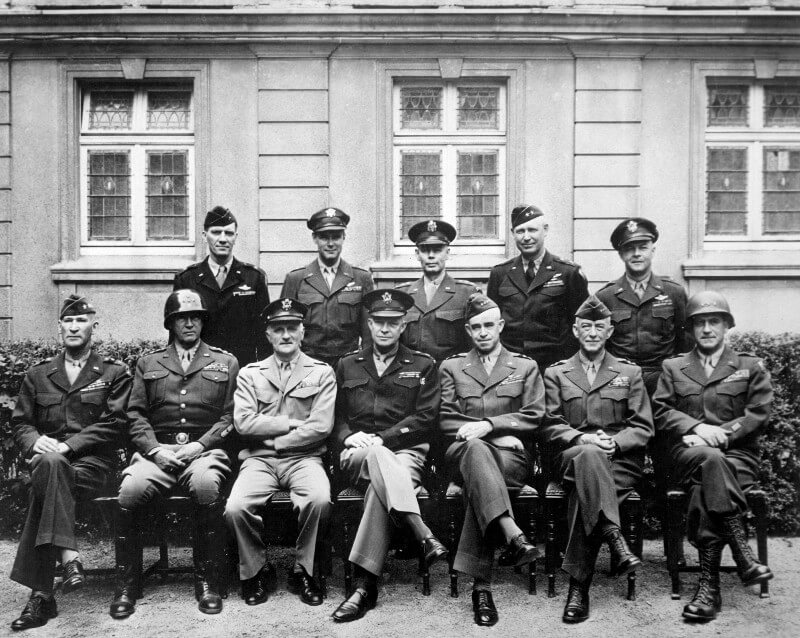 Formal black and white photo of General Dwight D. Eisenhower in US military uniform sitting with other generals during the Second World War
