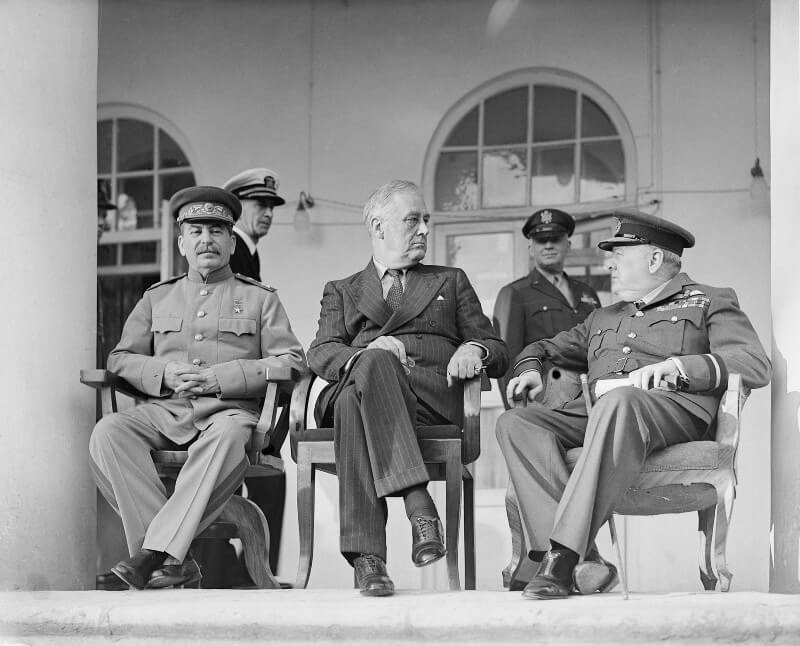 Photo of Franklin D. Roosevelt in a suit sitting with Winston Churchill in RAF uniform and Joseph Stalin in Soviet Soviet Union army uniform