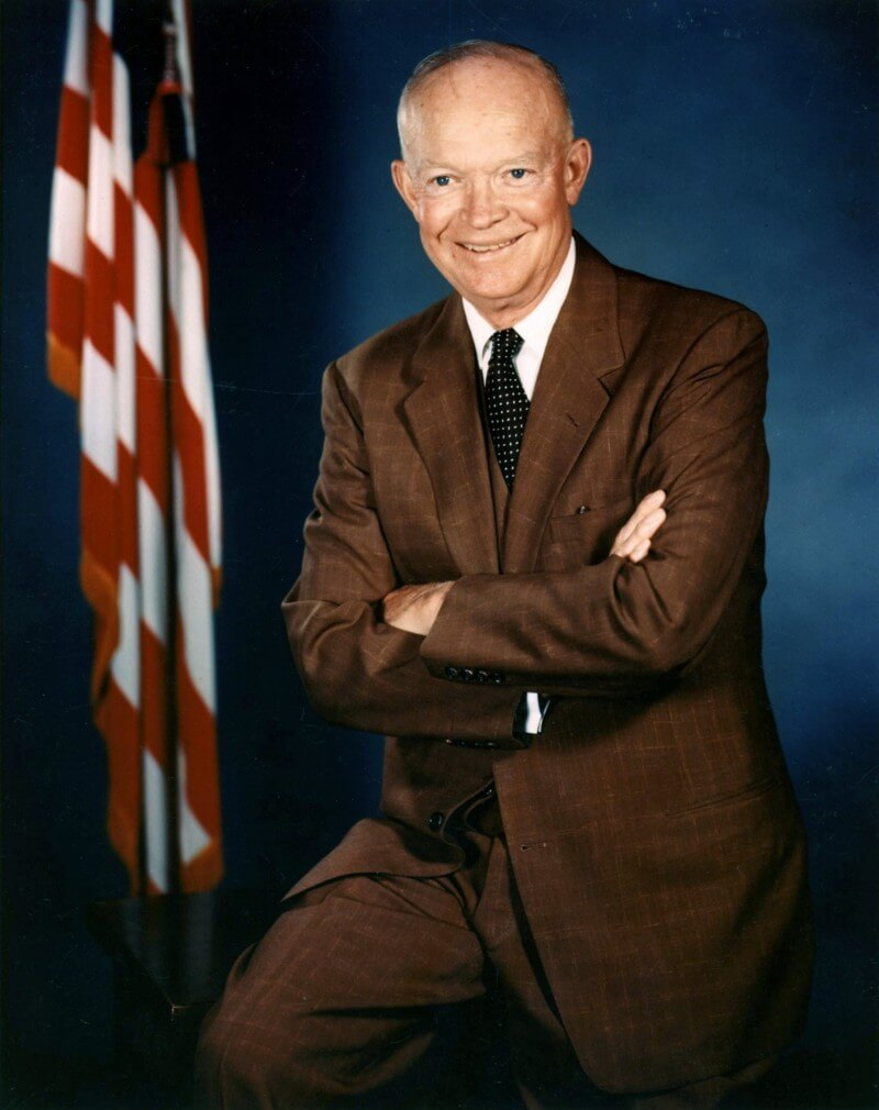 Official White House photo of Dwight D. Eisenhower, in color, folding his arms and smiling with large American flag in the background