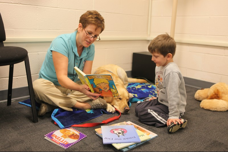 young boy reading a book to a golden retriever and trained facilitator