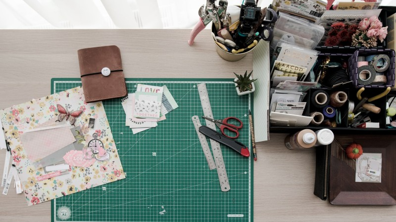 sewing supplies, including cutting mat, scissors and floral squares laid out on a table
