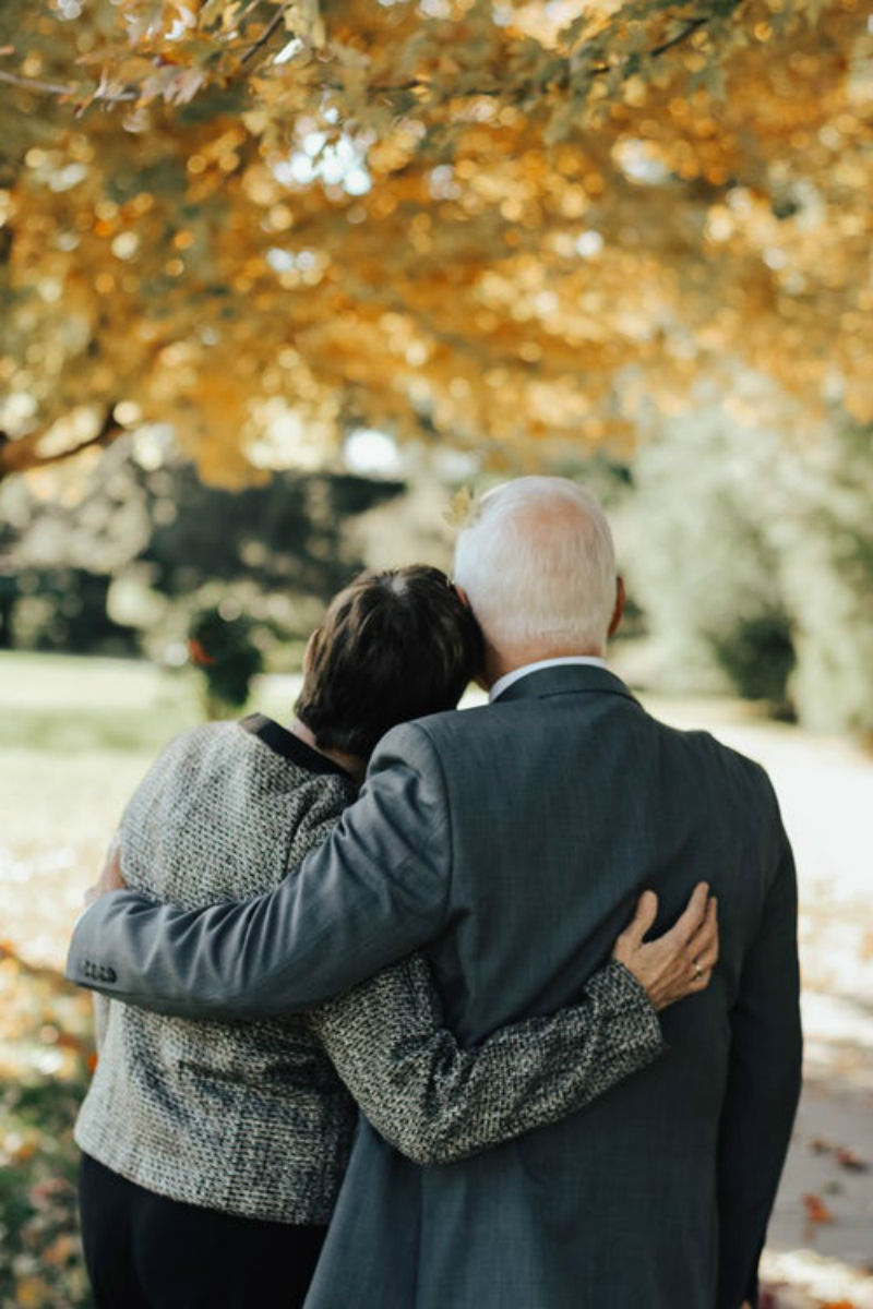 Rear view of an older man and woman with their arms round each other