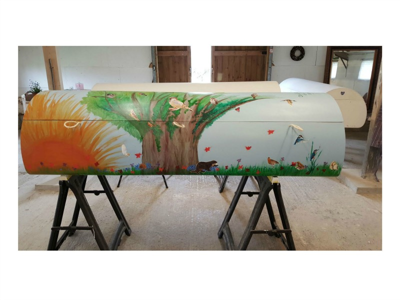 a curved coffin handpainted with trees and birds