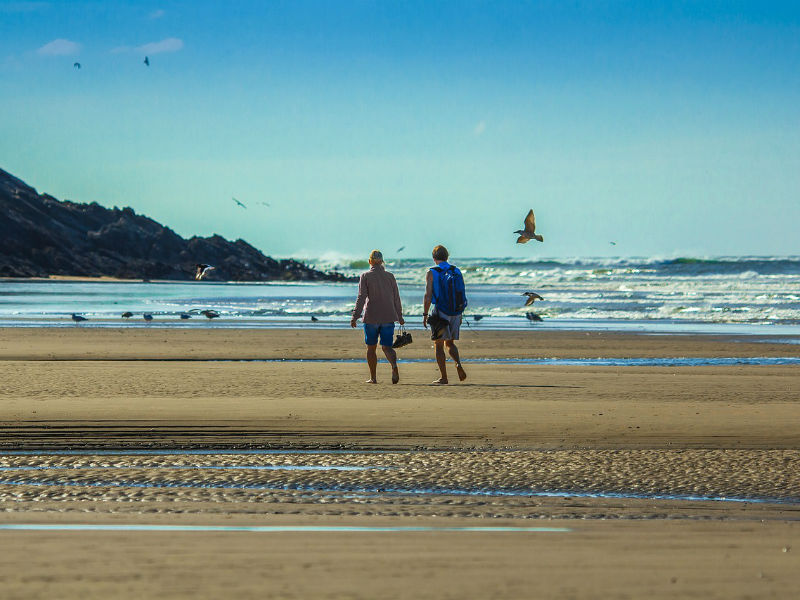 Two people in conversation as they walk on a beach