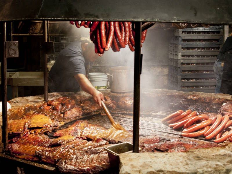 A chef cooking ribs and sausage over a BBQ pit