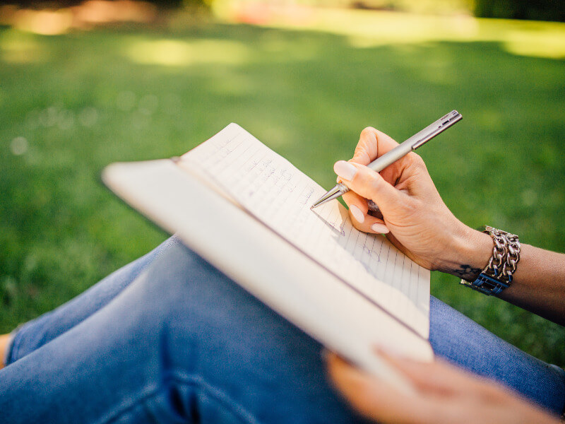Woman sitting outside writing in a diary for her bucket list