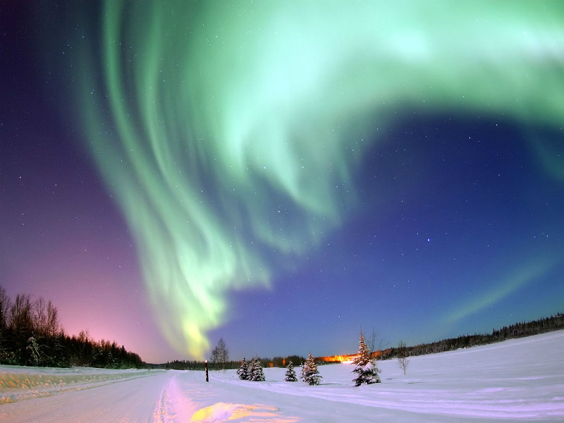 Green-colored northern lights above a snowy landscape