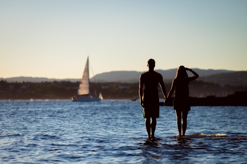 A man and woman in silhouette holding hands whilst standing on rocks and looking across a bay, with sailing boats in the background