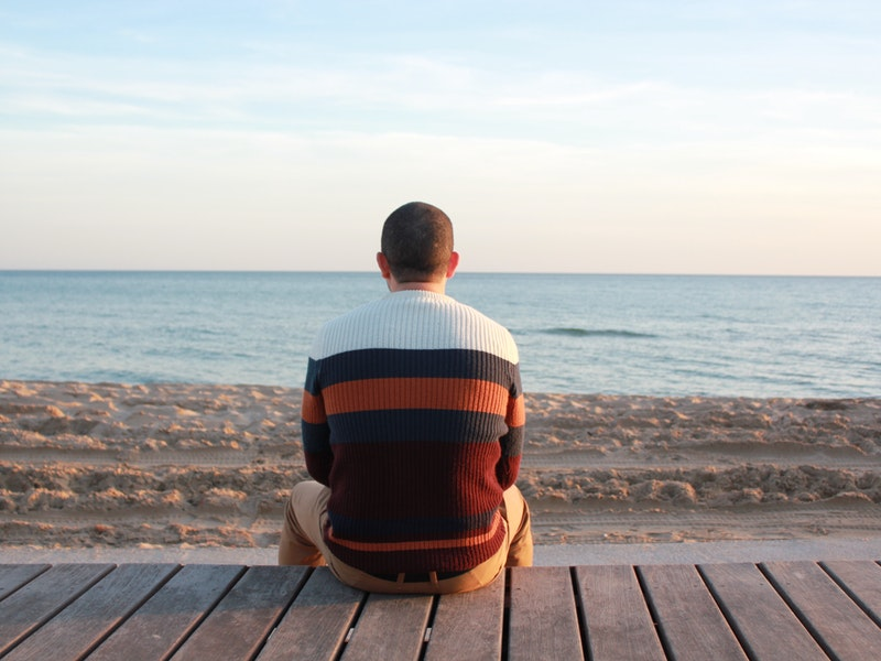 A man sitting by the beach and loking out to sea