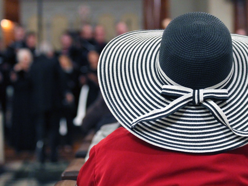 A woman in a large striped hat listening to a service!