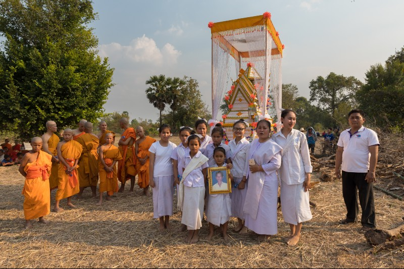 Buddhist children at a funeral, standing outside in front of the coffin with boys dressed as monks and girls in white clothes