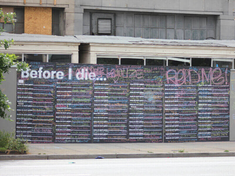 A Before I Die chalkboard next to a boarded up house