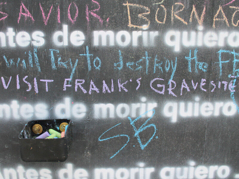 Close-up of a Before I Die chalkboard that reads, 'Visit Frank's gravesite