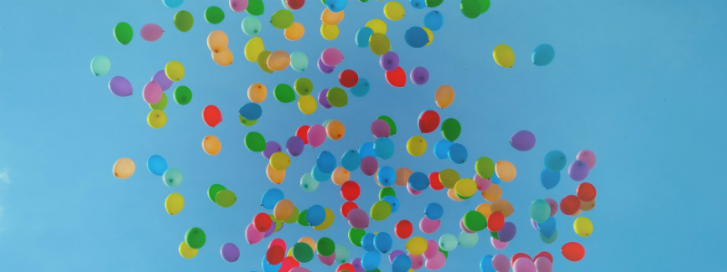 Multi-coloured balloons floating into the sky