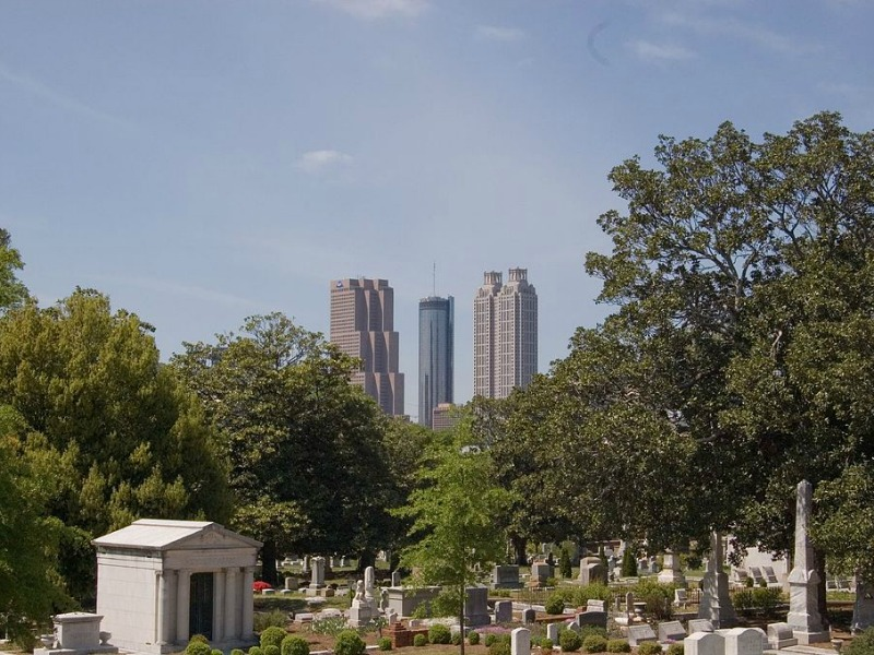 Oakland Cemetery looking green and tranquil on a summer day, with the city skyline behind