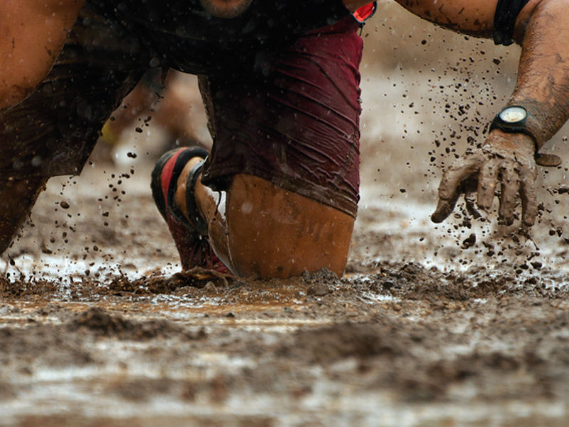 a runner slides through a muddy puddle