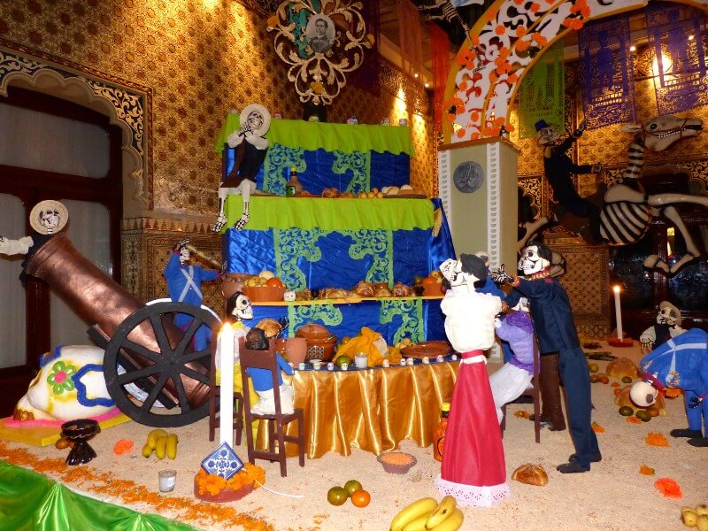 Photo of Mexican Day of the Dead shrine decorated with skeletons, bread, fruit, candles and paper decorations