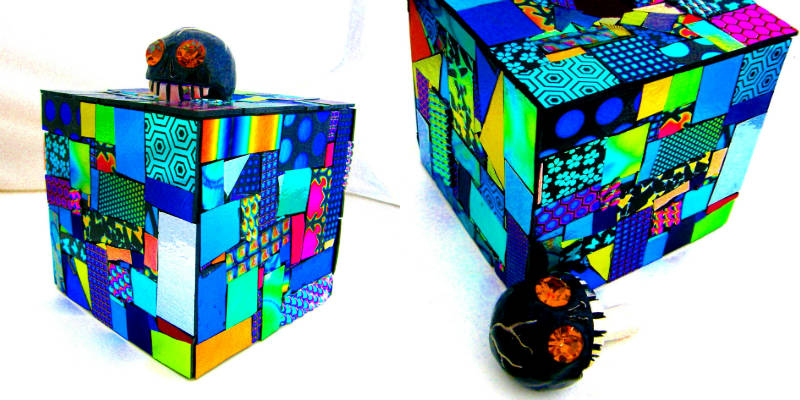 Cube-shaped urn with brightly coloured mosaic and skull-shaped stopper