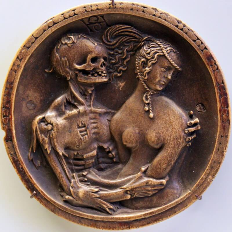 Photo of a circular wooden box with a carving of a women being embraced by a skeleton