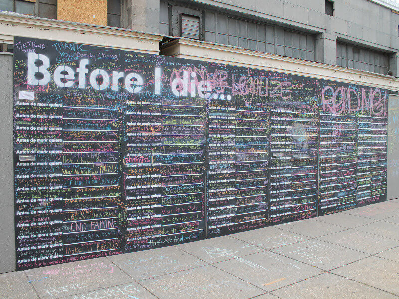 A large chalkboard wall with 'Before I die' written at the top, with hundreds of comments written in different coloured chalk