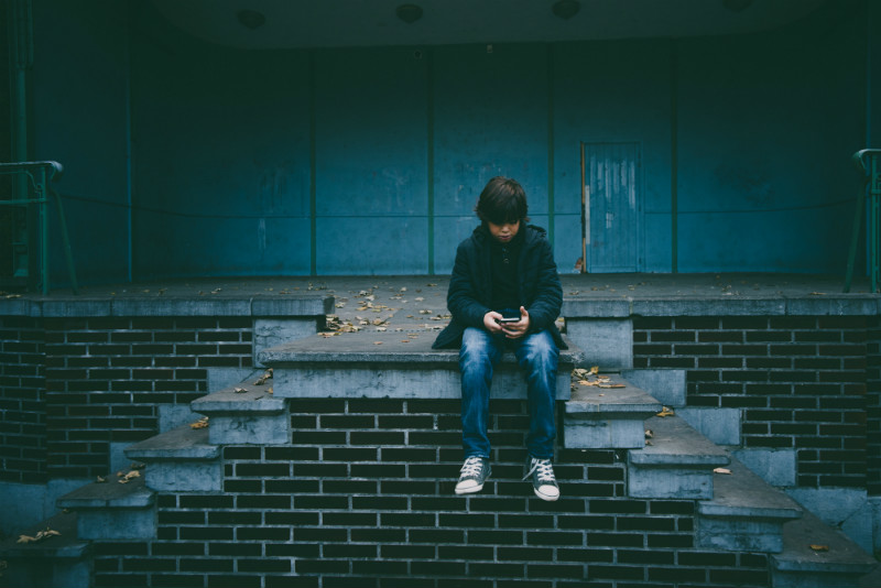 A boy sat on some steps, outside, looking sad