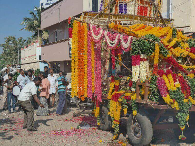 A funeral hearse laden with garlands of yellow, orange and pink flowers in India