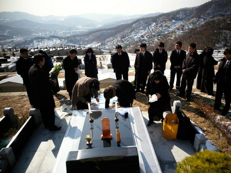 Korean mourners dressed in black, leaving offerings at a loved one's mountainside grave