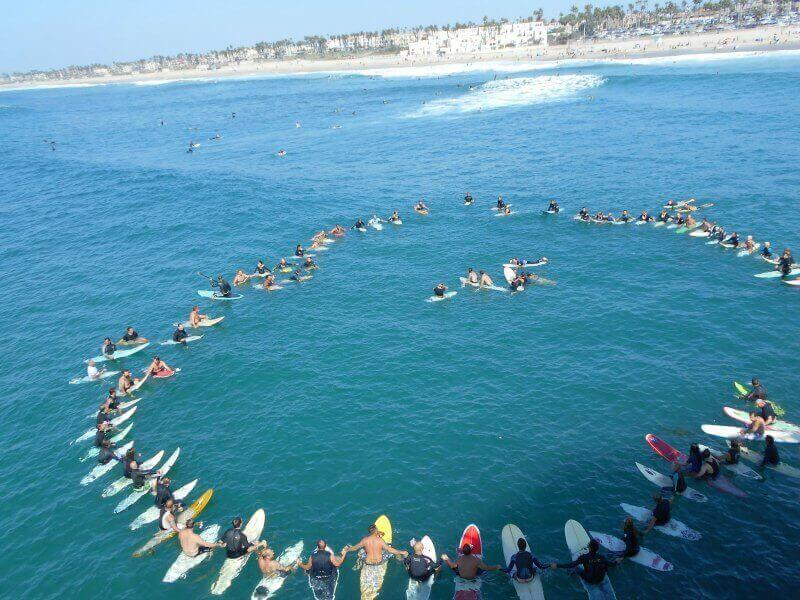 Around 50 surfers, sitting on their surfboards in the ocean, forming a circle and holding hands