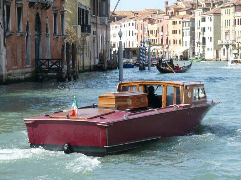 A motorboat with a casket on the back, driving down the Grand Canal in Venice