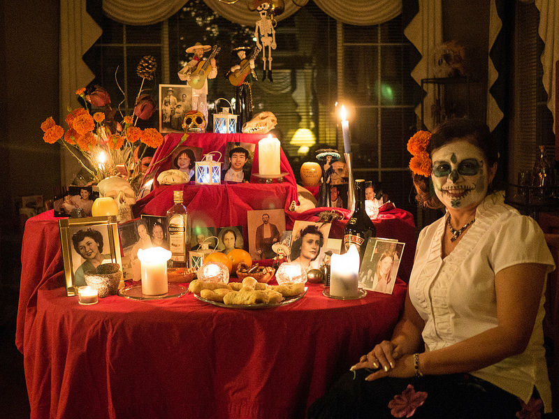 A smiling woman besides a shrine dedicated to family members who have died, on Day of the Dead