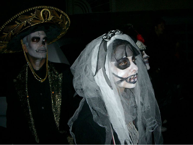 day of the Dead: People in calavera costume on a night time Dia de los Muertos procession