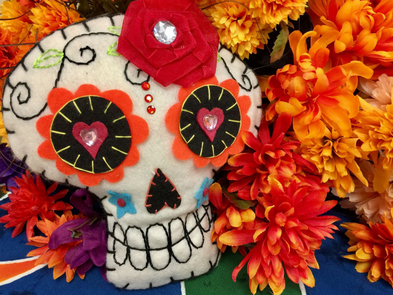 A crafted Day of the Dead skull with traditional marigolds