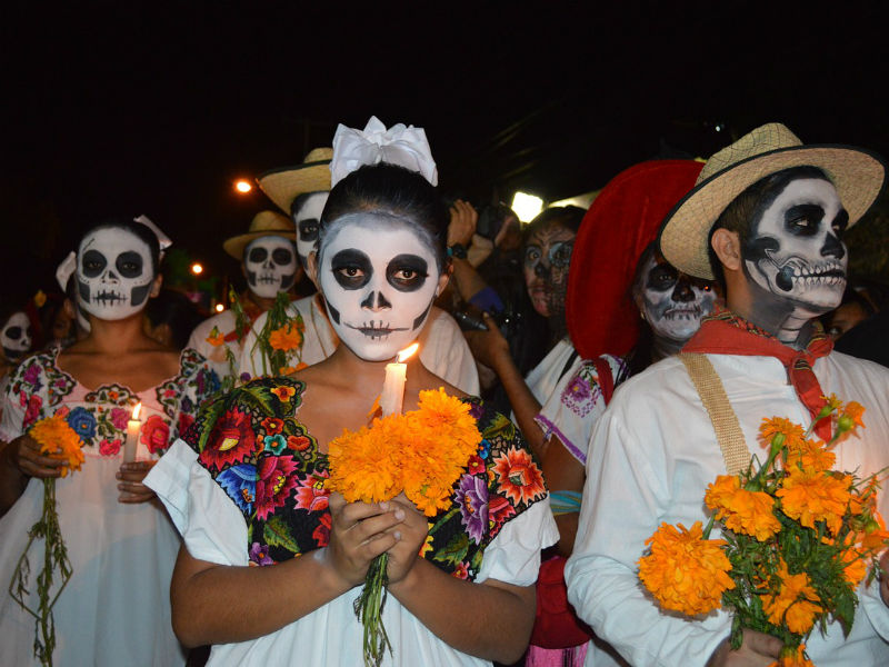 A colourful Day of the Dead procession with  gardlands of traditional marigolds