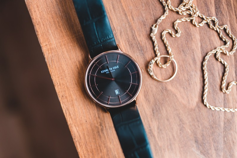 watch with a leather strap and a gold necklace chain lying on a wooden bench