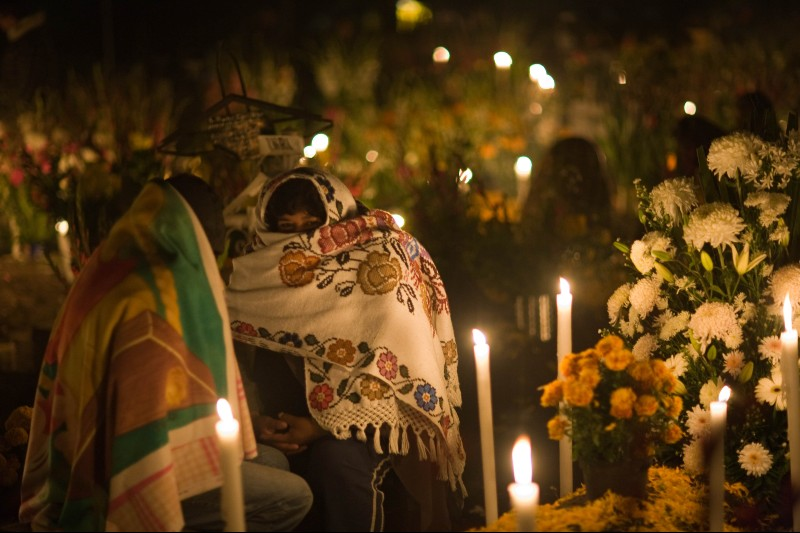 Photo of two Mexican woman in traditional shawls at the grave of a loved one who has died