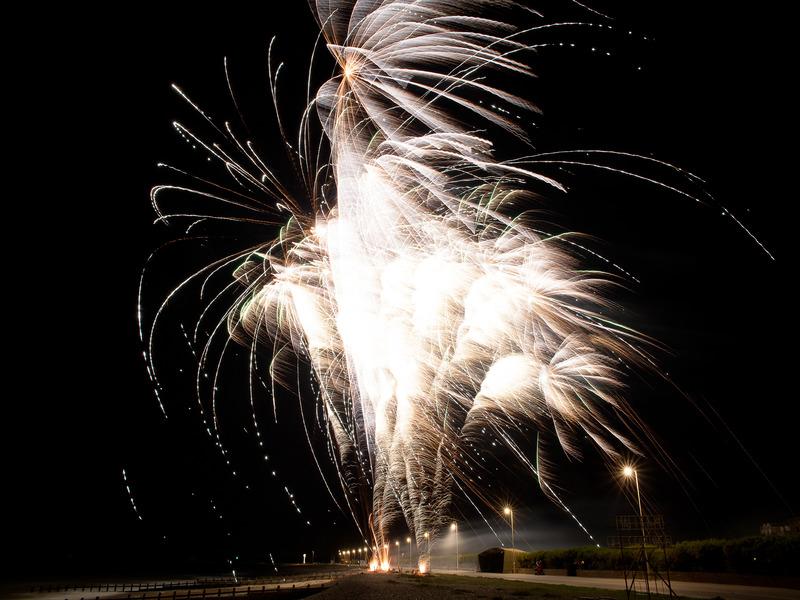 Huge white fireworks create jets of sparks flying upwards