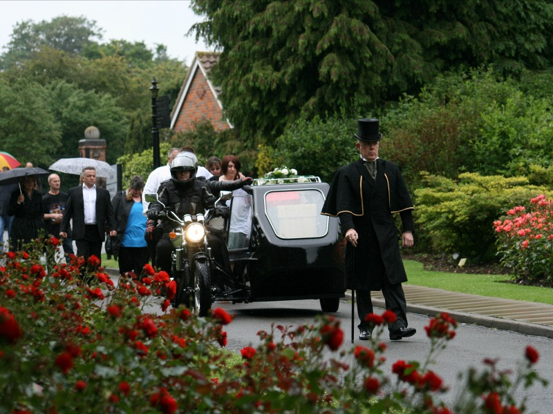 A motorcycle hearse arrives at the cemetery