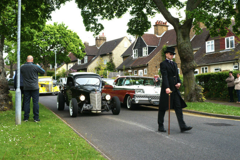A vintage hot rod is the hearse in a funeral procession making its way through a residential street