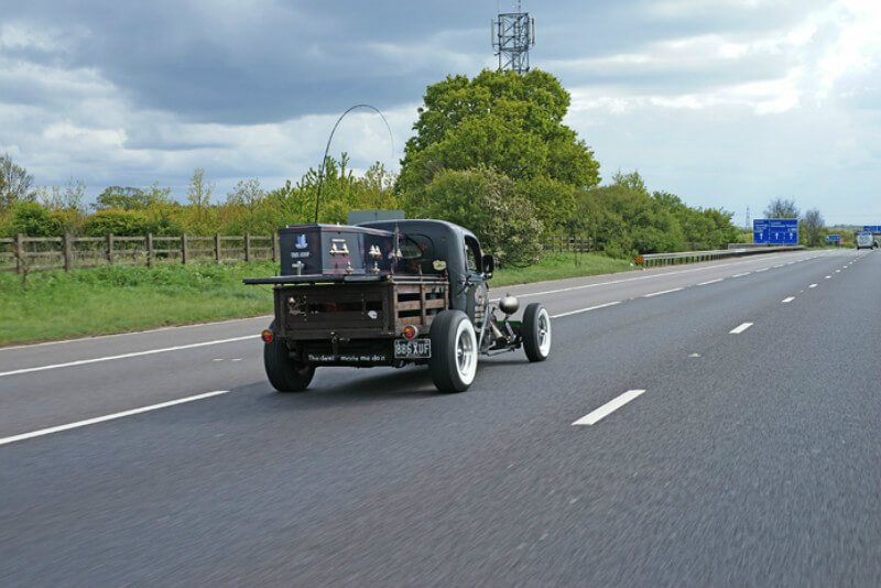 A coffins lies on the open deck of a hot rod hearse, which is making its way up an open dual carriageway