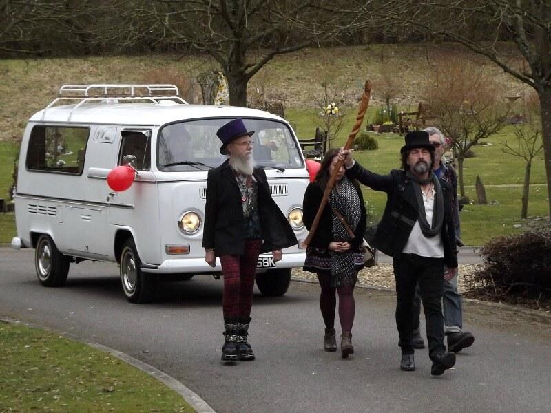 Mourners walk ahead of a VW campervan hearse